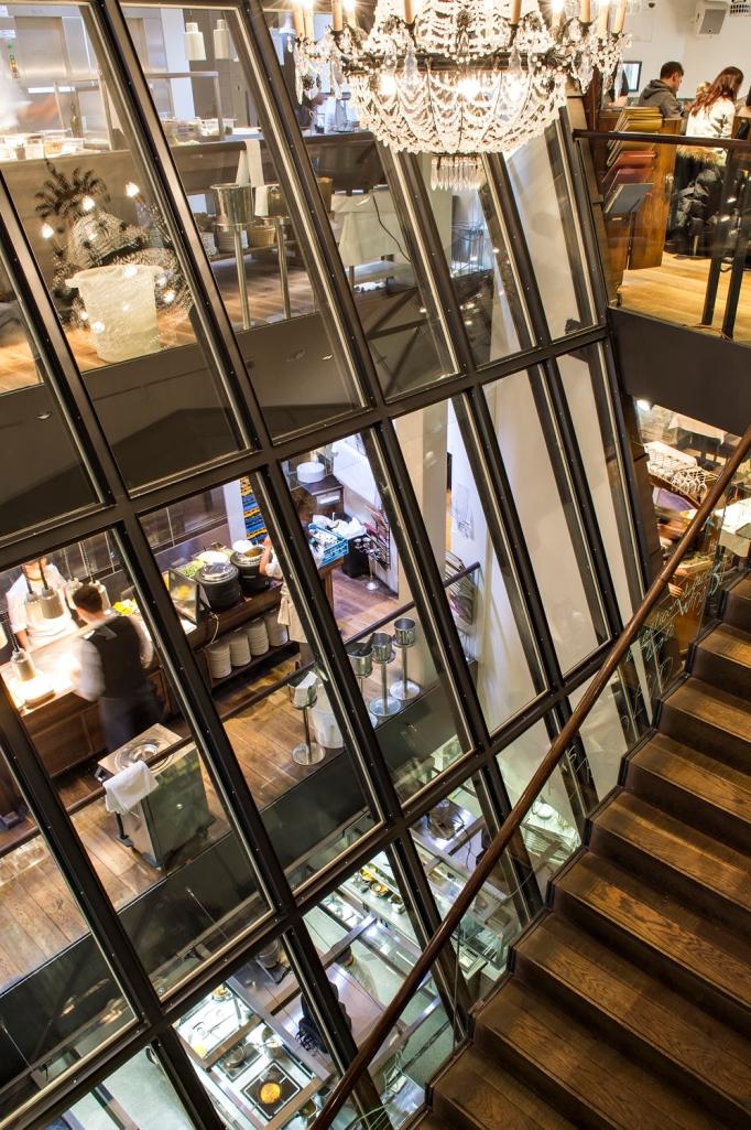Das gläserne Treppenhaus gewährt Einblick in die Küche.