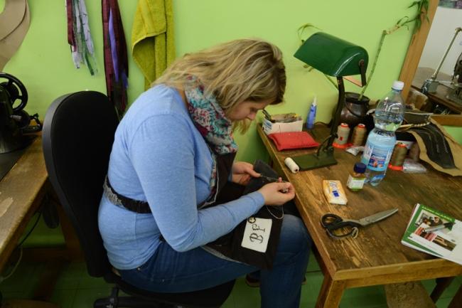 Die Säcklerin Bernadette beim Besticken einer Lederhose.