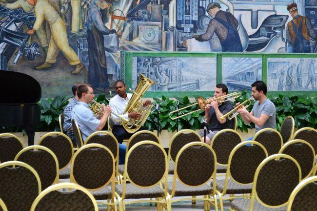 Orchester vor dem Diego Rivera Wandgemälde.