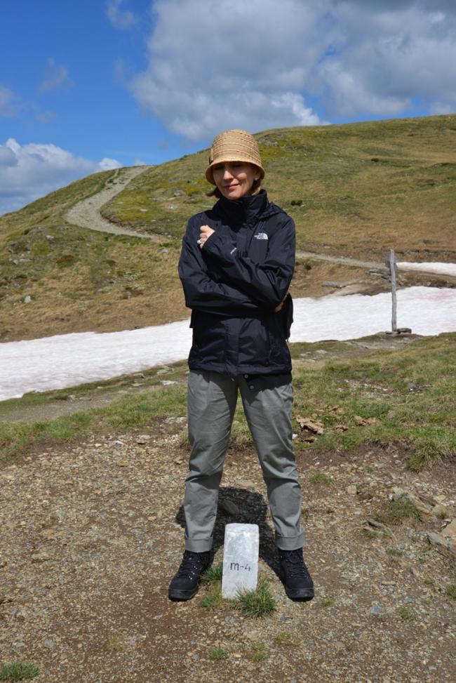 Grenzstein auf dem Helm. Mit einem Bein stehe ich in Italien, mit dem anderen in Österreich.